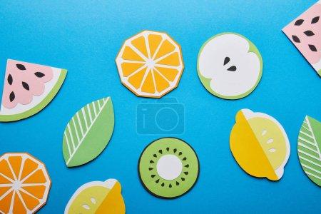 Foto de Vista superior de limones cortados en papel, hojas, naranjas, kiwi y sandiones sobre fondo azul - Imagen libre de derechos