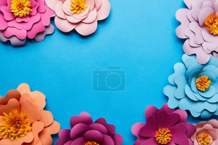 Photo for Top view of multicolored paper cut flowers on blue background with copy space - Royalty Free Image
