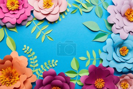 Photo for Top view of multicolored paper cut flowers with leaves on blue background with copy space - Royalty Free Image