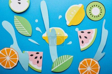 Photo pour Vue supérieure des éclaboussures d'eau coupées de papier avec des fruits sur le fond bleu - image libre de droit