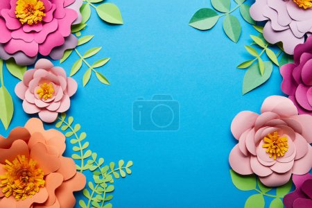 Photo for Top view of multicolored paper cut flowers with green leaves on blue background with copy space - Royalty Free Image