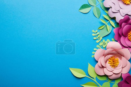 Photo for Top view of colorful paper cut flowers with green leaves on blue background with copy space - Royalty Free Image