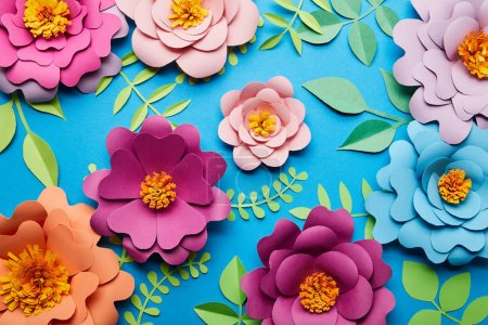 Photo for Top view of multicolored paper cut flowers with green leaves on blue background - Royalty Free Image