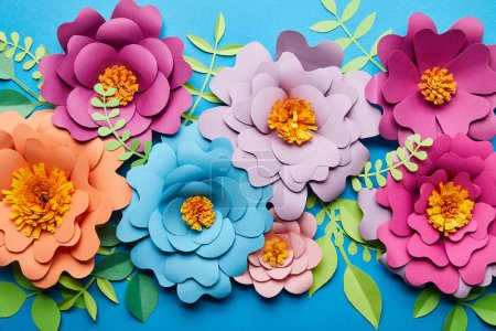 Photo for Top view of bright colorful paper cut flowers with green leaves on blue background - Royalty Free Image