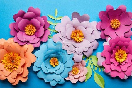 Photo pour Vue supérieure des fleurs coupées de papier colorées avec les feuilles vertes sur le fond bleu - image libre de droit