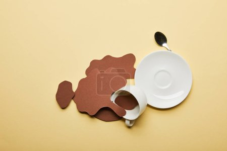 Photo for Top view of paper cut coffee spills near cup, saucer and spoon on beige background with copy space - Royalty Free Image