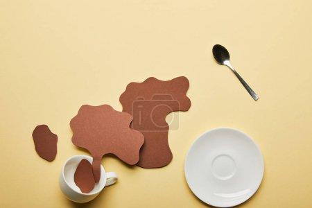 Photo pour Vue supérieure des déversements de café coupés de papier près de tasse blanche, de soucoupe et de cuillère sur le fond beige - image libre de droit