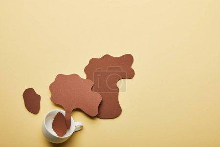 Photo pour Vue supérieure du papier coupé des déversements de café près de tasse sur le fond beige - image libre de droit