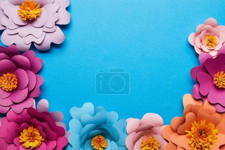 Photo for Top view of colorful paper cut flowers on blue background with copy space - Royalty Free Image