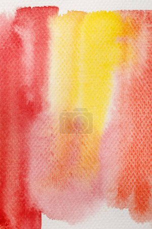 Photo for Close up view of pale yellow and red watercolor paint brushstrokes on textured background - Royalty Free Image