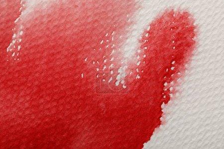 Photo pour Fermer vers le haut de vue de déversement rouge de peinture d'aquarelle sur le fond texturé blanc - image libre de droit