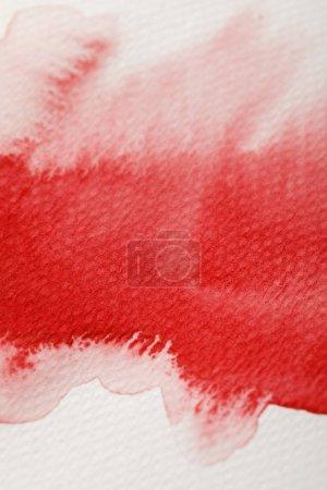 Foto de Vista de cerca de la pintura de acuarela roja derrame húmedo sobre fondo texturizado - Imagen libre de derechos