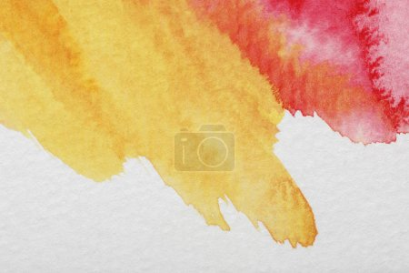 Photo for Close up view of yellow and red mixed watercolor paint spills on white background - Royalty Free Image