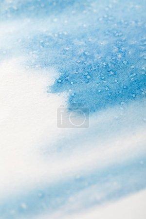 Foto de Close up view of blue watercolor paint brushstrokes with dots on white background - Imagen libre de derechos