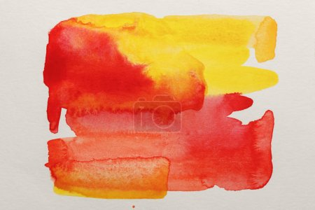 Photo for Top view of yellow and red watercolor paint spills on white paper - Royalty Free Image