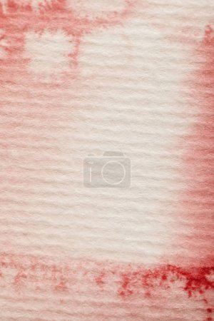 Photo for Close up view of red bright watercolor paint spill on textured paper background - Royalty Free Image
