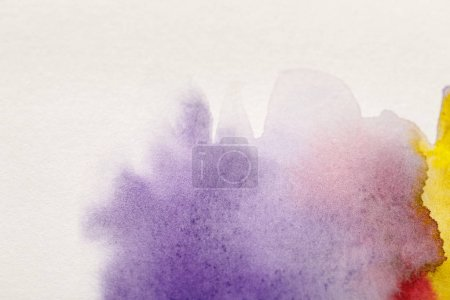 Photo for Close up view of yellow, purple and red watercolor paint spills on white background - Royalty Free Image