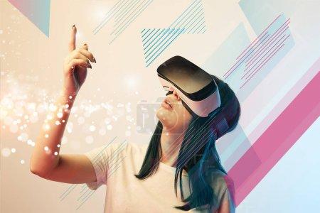 """Photo pour Une jeune femme dans un casque d """"écoute en réalité virtuelle pointant du doigt une illustration abstraite brillante sur fond beige - image libre de droit"""