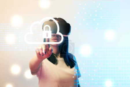 Photo pour Young woman in virtual reality headset pointing with finger at internet security illustration on beige and blue background - image libre de droit