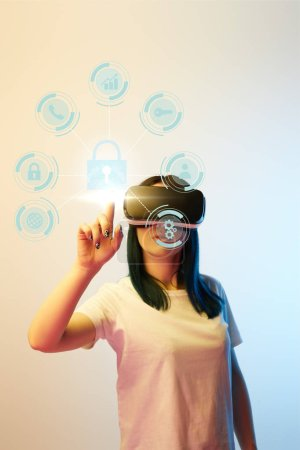Foto de Young woman in virtual reality headset pointing with finger at internet security icons on beige and blue background - Imagen libre de derechos