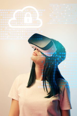 Photo for Young woman in virtual reality headset looking at internet security illustration on beige background - Royalty Free Image