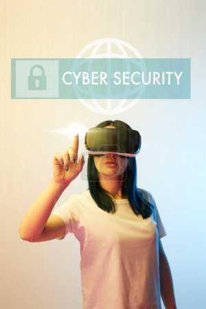 Photo pour Young woman in vr headset pointing with finger at cyber security illustration on beige and blue background - image libre de droit