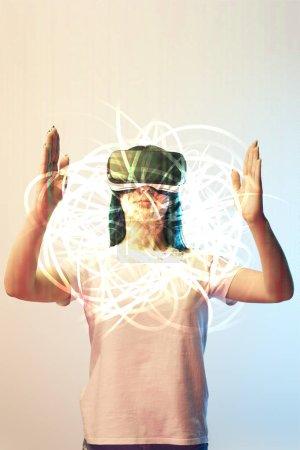 Photo pour Jeune femme en casque de réalité virtuelle tenant une illustration abstraite brillante sur fond beige et bleu - image libre de droit