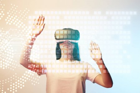 Photo for Young woman in virtual reality headset pointing with hands at glowing data illustration on beige and blue background - Royalty Free Image