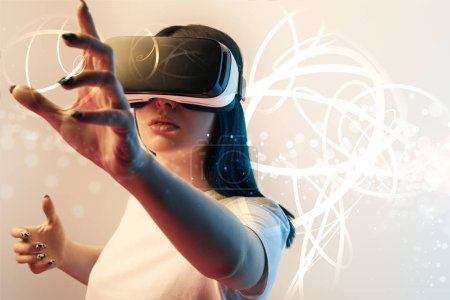 Foto de Young woman in virtual reality headset gesturing among glowing cyber illustration on beige and blue background - Imagen libre de derechos
