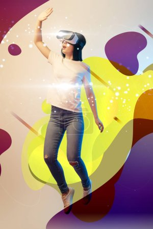Photo for Young excited woman in virtual reality headset levitating in air among glowing and abstract illustration on beige background - Royalty Free Image