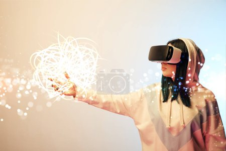 Foto de Young woman in virtual reality headset pointing with hand at glowing cyber illustration on beige and blue background - Imagen libre de derechos