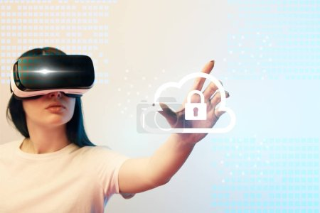 Foto de Young woman in virtual reality headset pointing with hand at internet security illustration on beige and blue background - Imagen libre de derechos