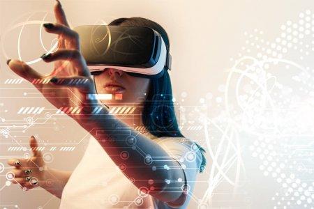 Photo pour Jeune femme en réalité virtuelle casque geste avec les mains parmi la cyber illustration rayonnante sur fond beige - image libre de droit