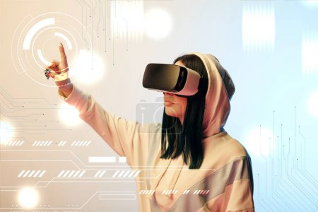 Foto de Young woman in virtual reality headset pointing with finger at glowing cyber illustration on beige and blue background - Imagen libre de derechos
