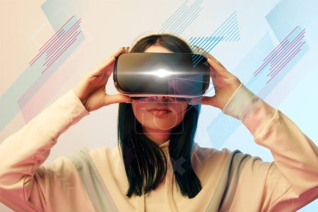 Foto de Young woman in virtual reality headset with glowing cyber and abstract illustration on beige and blue background - Imagen libre de derechos