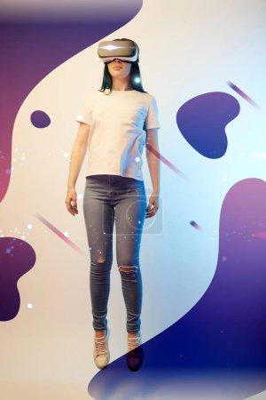 Photo pour Jeune femme en réalité virtuelle casque d'écoute lévitant en l'air parmi une illustration violette brillante et abstraite sur fond beige - image libre de droit