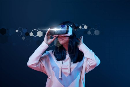 Photo for Young woman in virtual reality headset among cyber illustration on dark background - Royalty Free Image