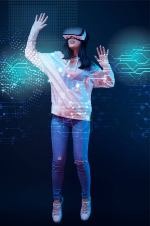 Foto de Young excited woman in virtual reality headset levitating in air among glowing data illustration on dark background - Imagen libre de derechos