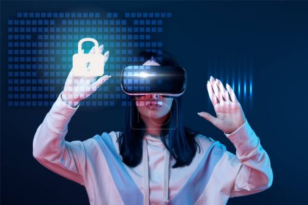 Foto de Young woman in virtual reality headset gesturing among glowing cyber security illustration on dark background - Imagen libre de derechos