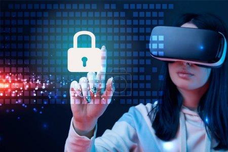 Photo pour Foyer sélectif de jeune femme dans le casque de réalité virtuelle pointant avec le doigt à l'illustration rougeoyante de cybersécurité sur le fond foncé - image libre de droit