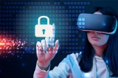 "Постер, картина, фотообои ""selective focus of young woman in virtual reality headset pointing with finger at glowing cyber security illustration on dark background"""
