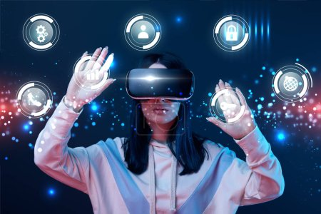 Photo for Young woman in virtual reality headset gesturing among glowing cyber icons on dark background - Royalty Free Image