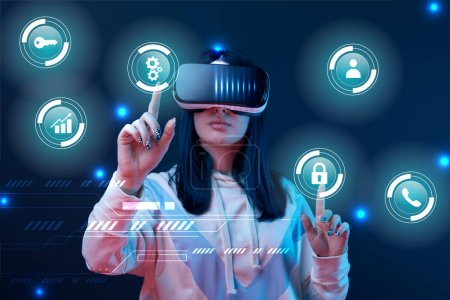 Foto de Young woman in virtual reality headset pointing with fingers at glowing cyber icons on dark background - Imagen libre de derechos