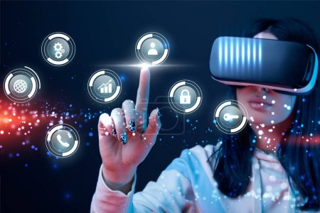 selective focus of young woman in virtual reality headset pointing with finger at glowing cyber icons on dark background