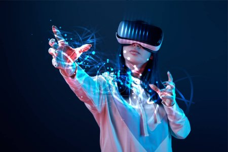 Photo for Young woman in vr headset gesturing among glowing cyber illustration on dark background - Royalty Free Image