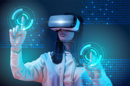 young woman in vr headset pointing with fingers at glowing cyber illustration on dark background