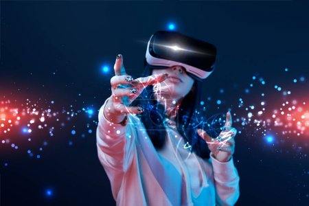 young woman in vr headset gesturing near glowing cyber illustration on dark background