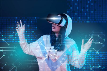 Foto de Excited young woman in vr headset gesturing near glowing data illustration on dark background - Imagen libre de derechos