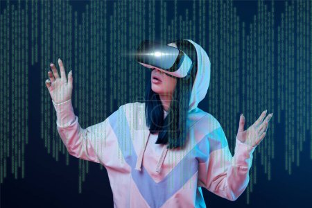 Photo for Excited young woman in vr headset gesturing near data illustration on dark background - Royalty Free Image