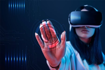 Photo for Selective focus of young woman in virtual reality headset pointing with hand at cyber illustration on dark background - Royalty Free Image